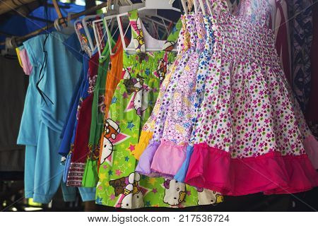 Dumaguete Philipines - 1 Nov 2017: children clothes selling in local village store. Cute baby girl dress on hangs. Nursery clothes for sale. Children wear on street market closeup photo. Pinoy store