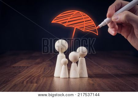 Family life and property insurance concept. Wooden figurines representing family and hand drawing umbrella symbol of insurance.