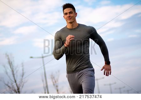 The smiling young sportsman is jogging and running as recreation outdoors.