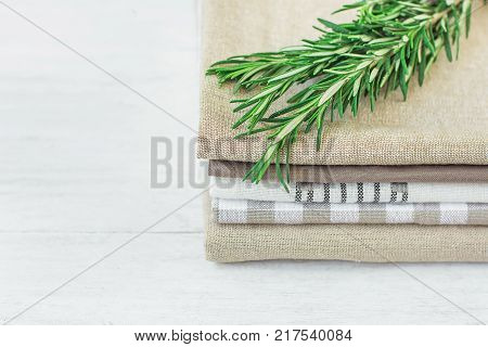 Stack of Linen and Cotton Kitchen Towels Napkins Fresh Rosemary Twig on White Wood Table Interior Design Website Store Banner Template Copy Space Provence Mediterranean Scandinavian