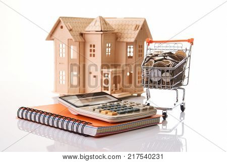 Home model, coins in shopping cart, note book and glasses over white background. Mortgage and real estate investment . Personal financial planning and online shopping concept