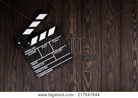Movie clapperboard on wooden table background flat lay, Work table of producer, the concept of movie, film, entertainment, advertising