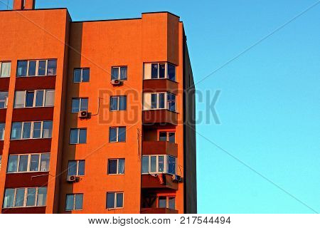 part of a brown high-rise building with balconies and windows on a blue background