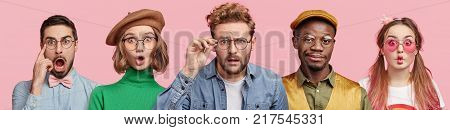 Composition of five different people wear spectacles look with surprised expression beig from various nations express shock and disbelief. Women and men stand in row isolated on pink background