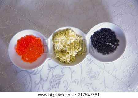 Red caviar, butter in a bowl Black caviar, above view of black dyed salty caviare of halibut fish in glass jar isolated on white background