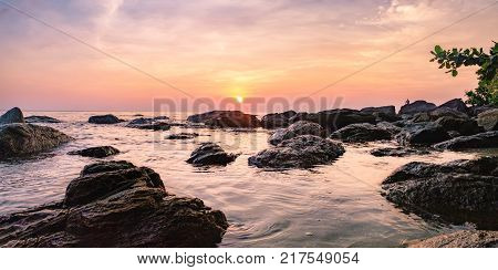 Tropical colourful sunset on the beach of Koh Chang island, Gulf of Siam, Thailand. Panorama view of dark night sea with protruding stones. A man sits on the rocks and admires the sunset