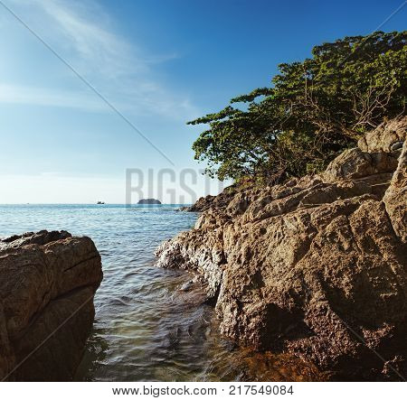 Beautiful seascape of White Sand Beach, Koh Chang island, Thailand. Nature composition. Scenic view with waves of the Gulf of Siam rolling on rocky shore ship to the horizon