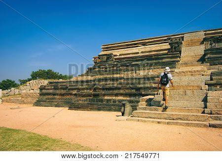 Hampi, India - November 19, 2012: An unidentified tourist climbs the stairs to the platform of Mahanavami Dibba in Hampi, Karnataka, India.