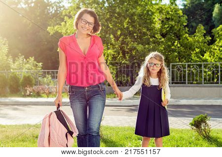 Mom and pupil of elementary school  holding hands. The parent takes the child to school. Outdoors, return to the concept of the school.