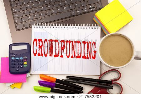 Word writing Crowdfunding in the office with  laptop, marker, pen, stationery, coffee. Business concept for Business Fundraising Project Funding Workshop white background with space