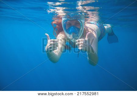 Woman snorkeling showing thumbs. Snorkel in full face mask. Female swim with loose red hair. Beautiful girl in water. Underwater photo shot in ocean. Tropical vacation activity or sport in blue sea