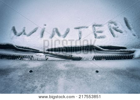 The word winter is written on the snow covering the car's windshield in december