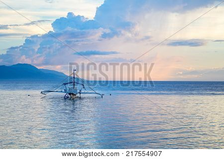 Seaside sunset with orange and blue clouds. Tropical sea and distant island in sunset colors. Idyllic seaview with rustic boat. Philippines seascape. Romantic pink landscape of sea and tropic sunset
