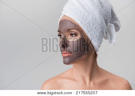 Middle-aged attractive naked woman with towel on head is looking aside thoughtfully while standing with facial clay mask. She is using anti-aging procedures. Isolated with copy space. Skincare concept