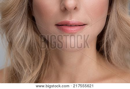 Close-up of lips of middle-aged charming pleasant blond woman