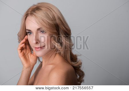 Mysterious beauty. Sensual elegant middle-aged naked woman is standing and touching her face while looking aside thoughtfully. Isolated background with copy space in the right side