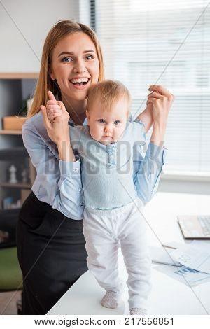 Full length portrait of calm kid going on table while keeping happy mom by arm. Labor and family concept