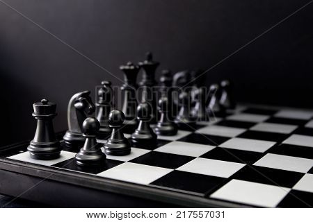 Black chess figures on board. Black chess set in order for game start. Black chess figures row on checkered board. game begins. Checkmate game banner template. Intellectual sport. Tactic game