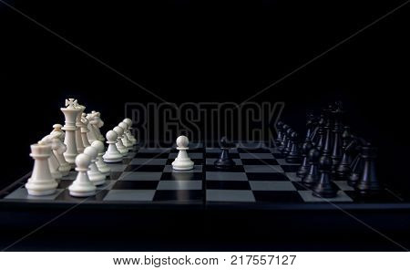 White pawn and black pawn on chess table. Black chess set in order for game start. Chess competition first move. Checkmate game banner template. Business competition with equal opportunities concept