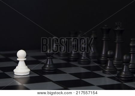 White pawn and black pawn on chess table. Black chess set in order for game start. Chess competition first move. figurine order. Checkmate game banner template. Strategic competition concept