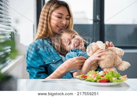 Playful parent and child are eating salad at home. Mother is embracing girl with love while kid is holding soft toy. Happy motherhood concept