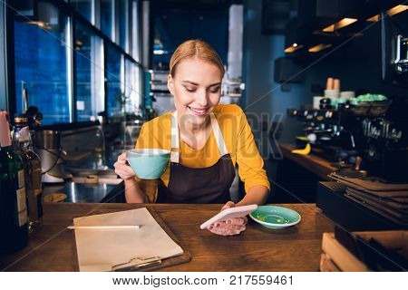 Portrait of smiling girl barista typing in mobile while tasting cup of coffee at table in confectionary shop. Rest concept