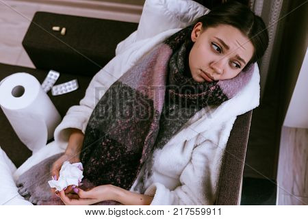 sad young girl got sick with angina because of cold weather, a warm scarf around her neck, looks sadly out the window
