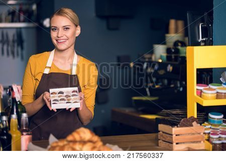 Portrait of happy seller holding candies in hands while standing at counter in confectionary shop. Job concept