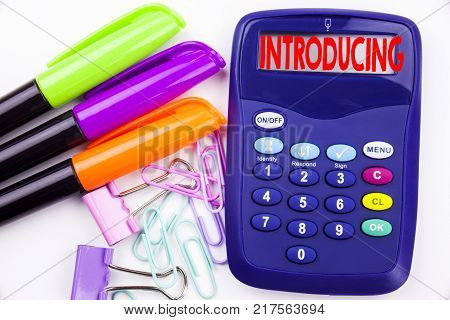 Writing word Introducing text in the office with surroundings such as marker, pen writing on calculator. Business concept for Introduction Start Intro Beginning white background with space