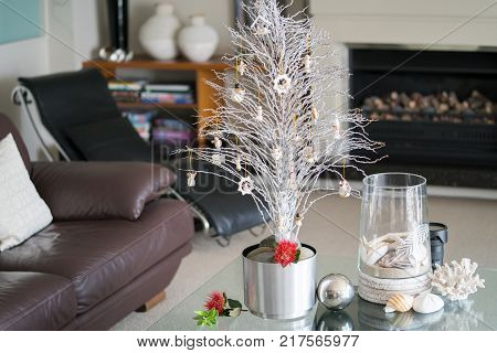 Simple summer New Zealand theme Christmas small white tree on glass table with seaside vase decoration and bright red pohutukawa flower in lounge.