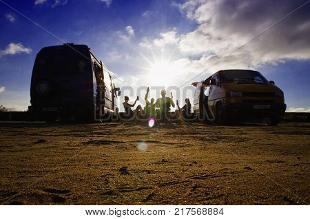 Party on the beach. Travellers having a party on the beach. Two couples spend the holiday together. Travelling in the van concept.