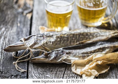 fish pike dried with a glass of beer on wooden boards