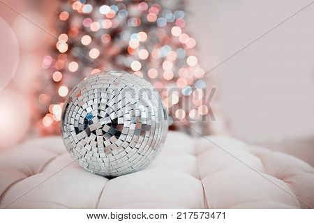 Disco ball. Close-up of a mirror ball against the backdrop of a Christmas tree and garland lights. Concept Christmas, party.