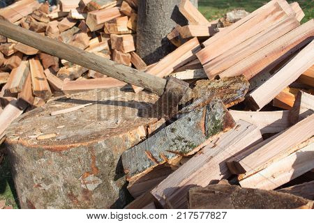 axe in log stack of firewood. Axe ready for cutting timber. a pile of freshly chopped wooden logs