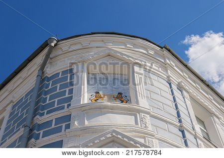 round the corner of an old building with bas-reliefs and ornaments. blue sky. the oldest music school in Vladimir
