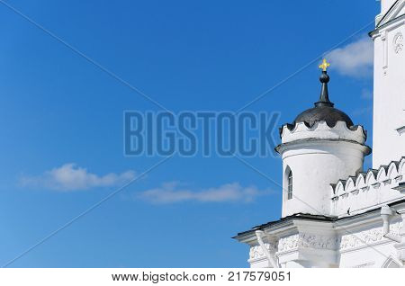 a small stone tower with an arched window and a cross on the end of the ancient white buildings against the blue sky