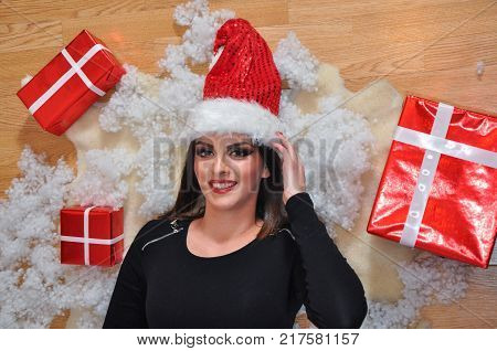 Beautiful smiling girl with Santa Claus cap lying on the floor with a New Year's decoration.