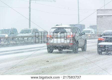 KYIV UKRAINE - NOVEMBER 29 2016: The transport movement at the Moscow bridge during a snow storm. Kiev Ukraine