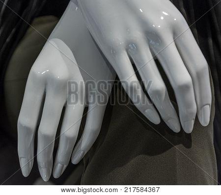 crossed mannequin tenders hands on gray background .