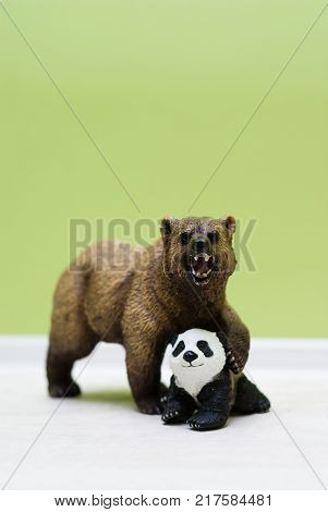 A toy grizzly bear protects a toy little panda. Maternal instinct