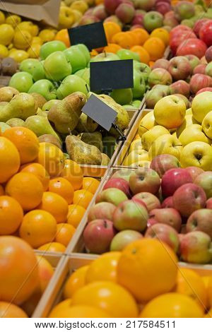 attractive fruit stall with price tags in store .