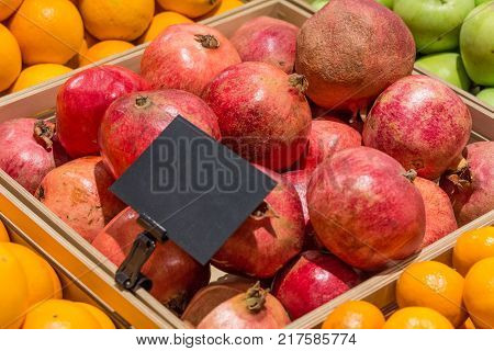 Pomegranates in a wooden box with a price tag
