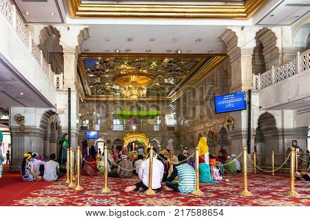 NEW DELHI INDIA - MARCH 18 2016: Horizontal picture of indian people of Sikh religion praying inside Gurudwara Sisganj Sahib located in New Delhi India.