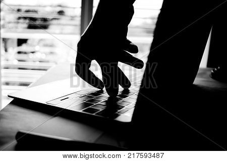 Cyber crime hand reaching out through laptop computer and attack signifying in internet theft while using online banking Payment Security Concept. Anonymous Hacked in Black