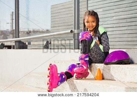 Cute African girl in roller blades sitting on the stairs of skate park at sunny day