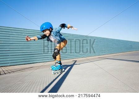 Side view portrait of preteen boy, roller skater in helmet and protective gear, skating fast at outdoor rollerdrom