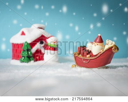 Happy Santa Claus with gifts box on the snow sled going to snow house. near snow house have Snowman and Christmas Tree. Santa Claus and snow house on the snow the background is powder blue.