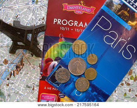 Symbols of Paris and France in flat layout or background. Eiffel tower, guide to Paris with map and program for theme park, old French coins francs and centimes. Vacation tour or tourist journey to Europe. Editorial only. The map used in composition, has