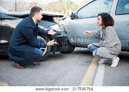 Man and young woman arguing after bad car crash