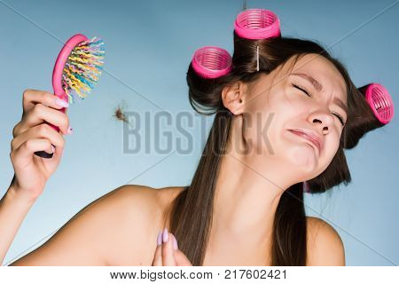 sad young girl does her hair with a curler, loses her hair, cries poster
